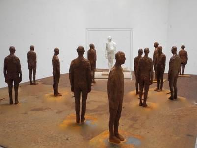 Anne Haring, Figur im Raum, Installation (mit 18 Figuren der F-Serie, Tisch-Sockel), Eisen/Acryl/Holz/Plastilin, 2019